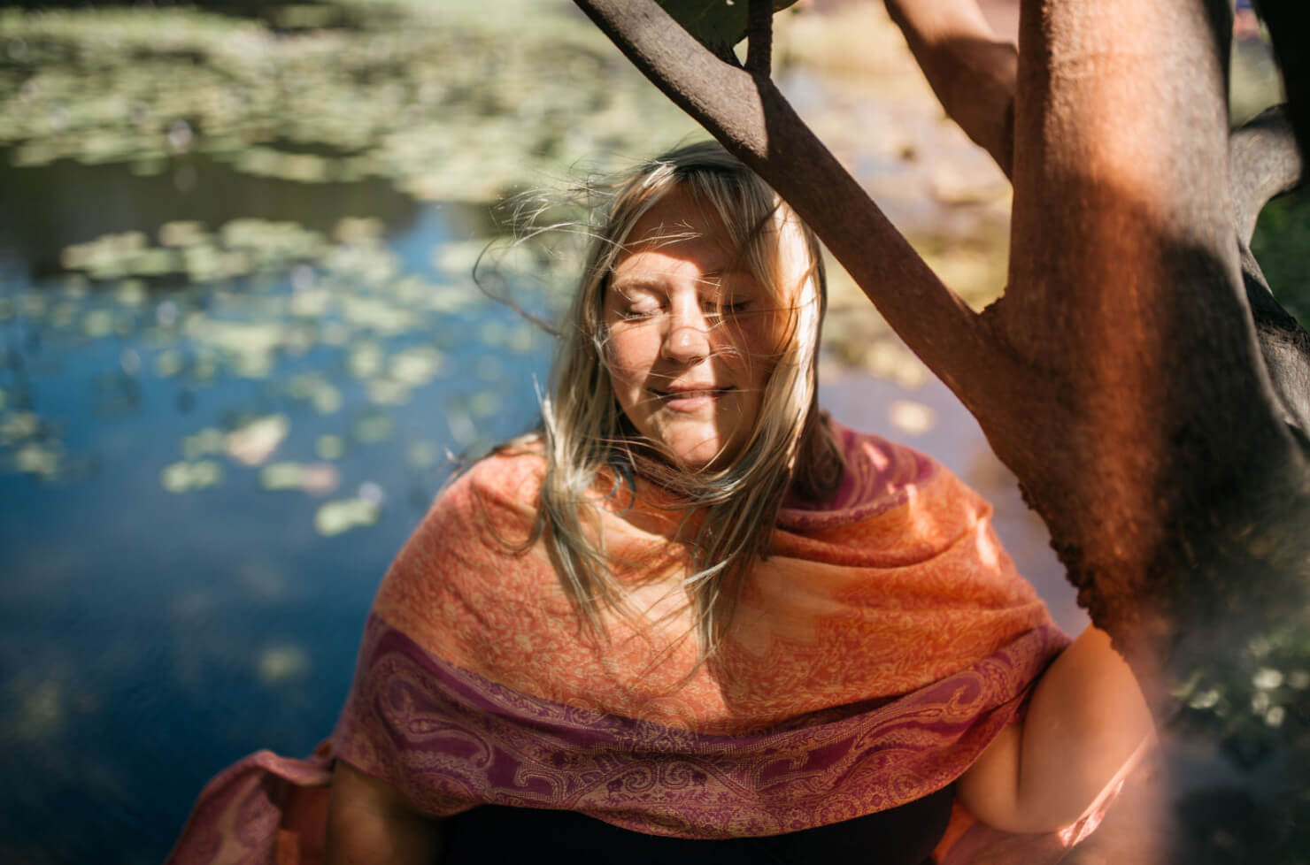 Woman eyes closed in front of river