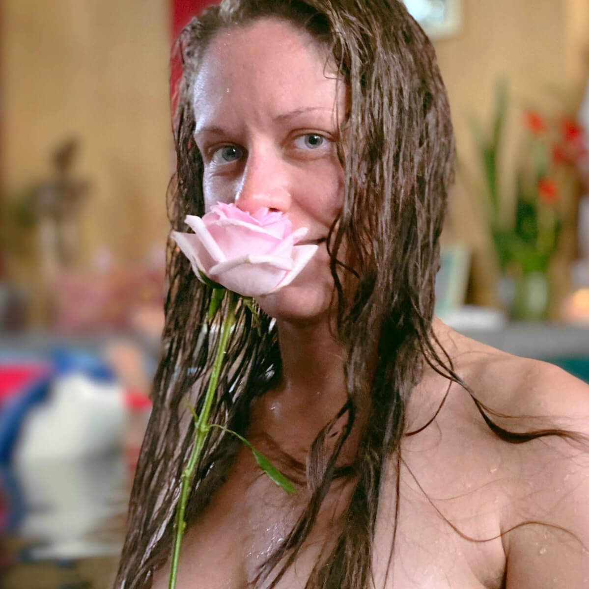 Woman wet with flower in front of her face