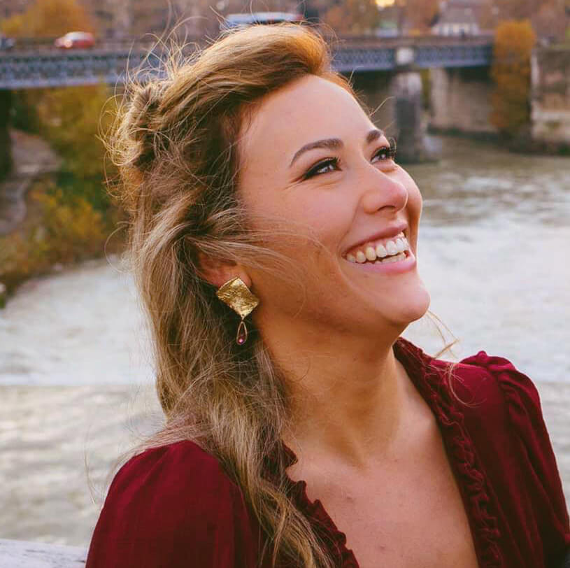 Woman smiling staring up with big earings